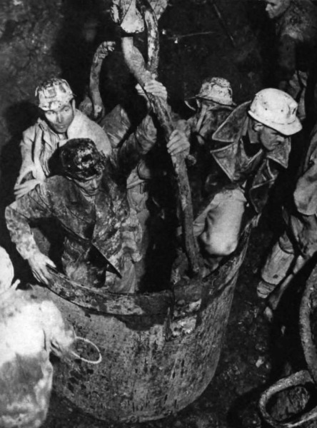 "Five men, shaft-sinking crew, in a ""hoppit.""  Left to right, Bill Chambers, Joe Chantry, Arthur Miller, ""Pom"" Leverton, Arthur Chamberlain and, top right in the shaft, ""Taff"" Lawson."